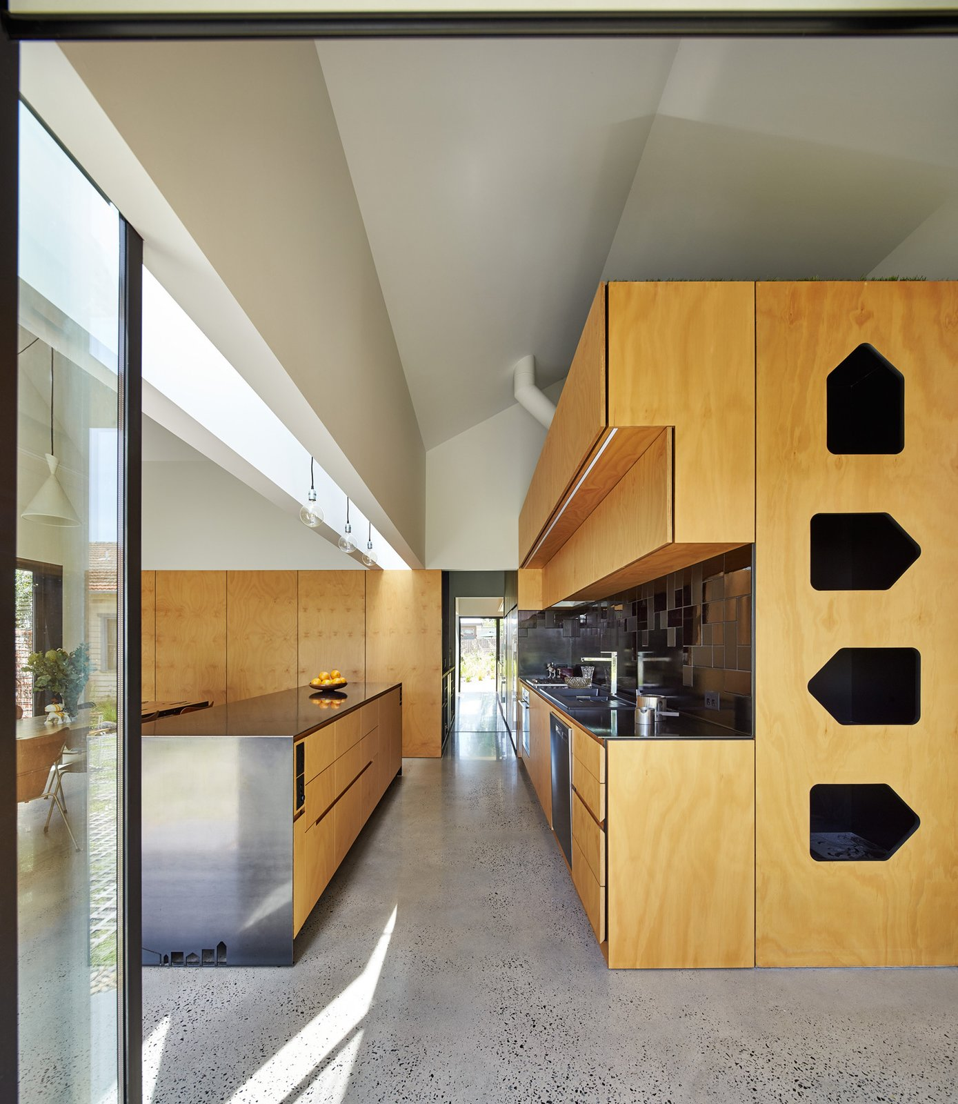 """The house's dominant gable form repeats at a smaller scale throughout the dwelling, as in the kitchen's plywood and steel cabinets. """"The gable became thematic throughout the process,"""" Maynard explains. """"Whenever issues arose, we referred back to it as a default, rather than adding a new idea."""" The sink is by Abey, faucet by Franke, and range by Qasair. Tagged: Kitchen, Wood Cabinet, Concrete Floor, and Metal Counter.  Photo 9 of 12 in This Transformed Melbourne House Resembles a Quirky Village"""