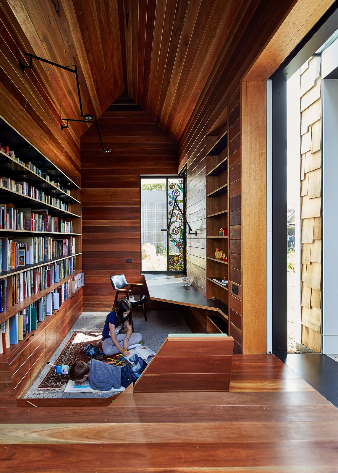 """The library is lined in reclaimed spotted gum that Maynard says """"brings with it wisdom from its previous life."""" A stained glass window by Leigh Schellekens makes the contemplative room feel like a domestic chapel. Tagged: Office, Library, Medium Hardwood Floor, and Bookcase.  Read by DAVE MORIN from This Transformed Melbourne House Resembles a Quirky Village"""