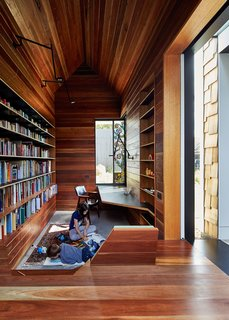 "This Transformed Melbourne House Resembles a Quirky Village - Photo 9 of 11 - The library is lined in reclaimed spotted gum that Maynard says ""brings with it wisdom from its previous life."" A stained glass window by Leigh Schellekens makes the contemplative room feel like a domestic chapel."