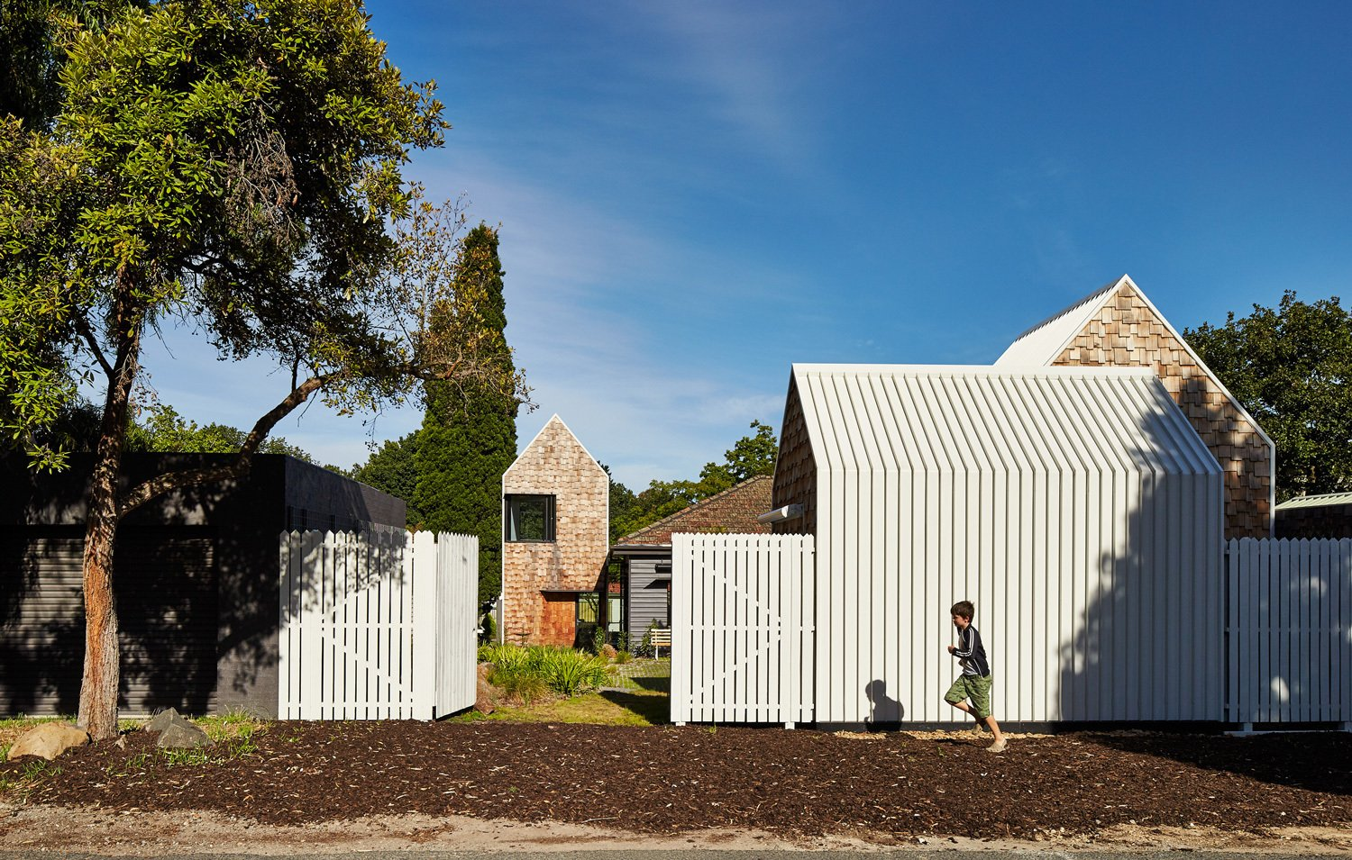 A small country road borders the property to the west. Tagged: Outdoor, Vertical Fence, and Wood Fence. This Transformed Melbourne House Resembles a Quirky Village - Photo 12 of 12