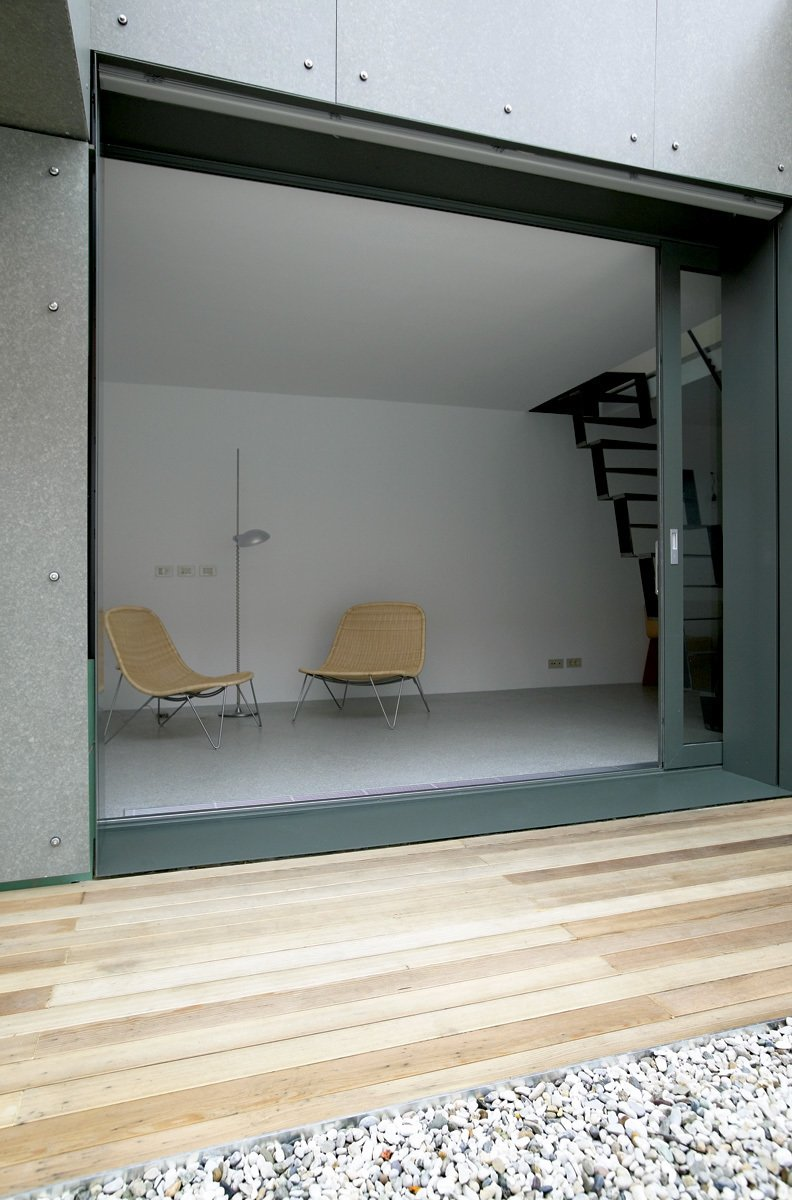 A wall-sized sliding window opens the downstairs living area up to a intimate atrium-style outdoor area. A narrow deck, which is screened from the surrounding houses, brings an astonishing amount of indirect sunlight into the ground floor.  190+ Best Modern Staircase Ideas by Dwell from 100-Year-Old Service Shed in Slovenia Becomes a Miniature Home