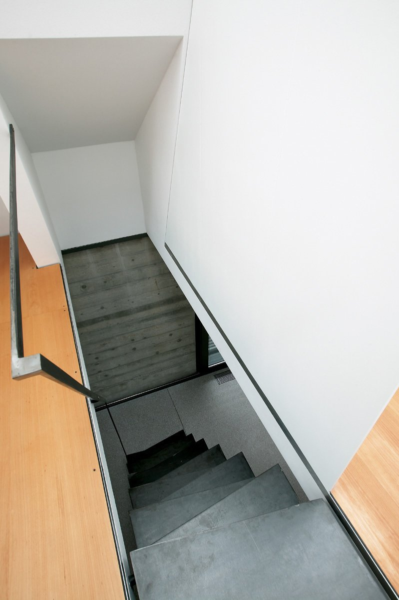 A view from above of the iron staircase, which faces one of the textural béton brut cement walls. Its treads slant at opposing angles, creating their own minimal pattern.