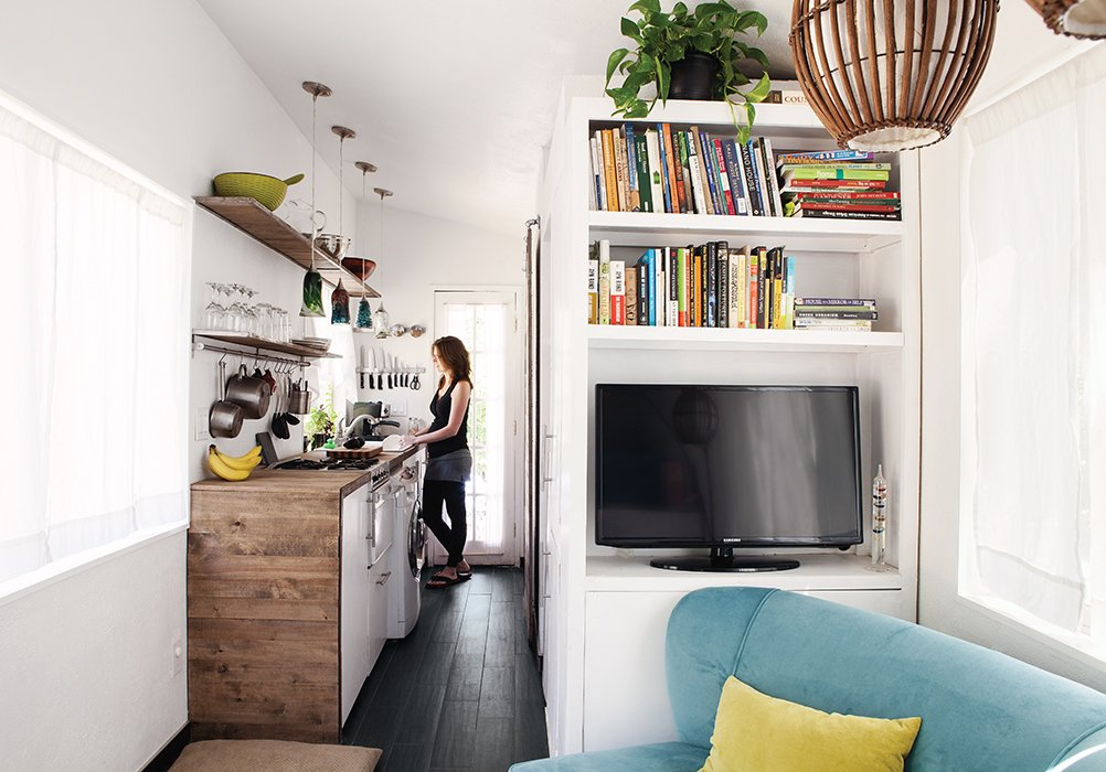 An enthusiastic cook, Miller says she can easily work in the galley-style kitchen. The reclaimed-wood surround echoes the exterior cladding. Tagged: Living Room, Chair, Shelves, Dark Hardwood Floor, and Pendant Lighting.  Photo 2 of 4 in Tiny House Fits a Family in 196 Square Feet