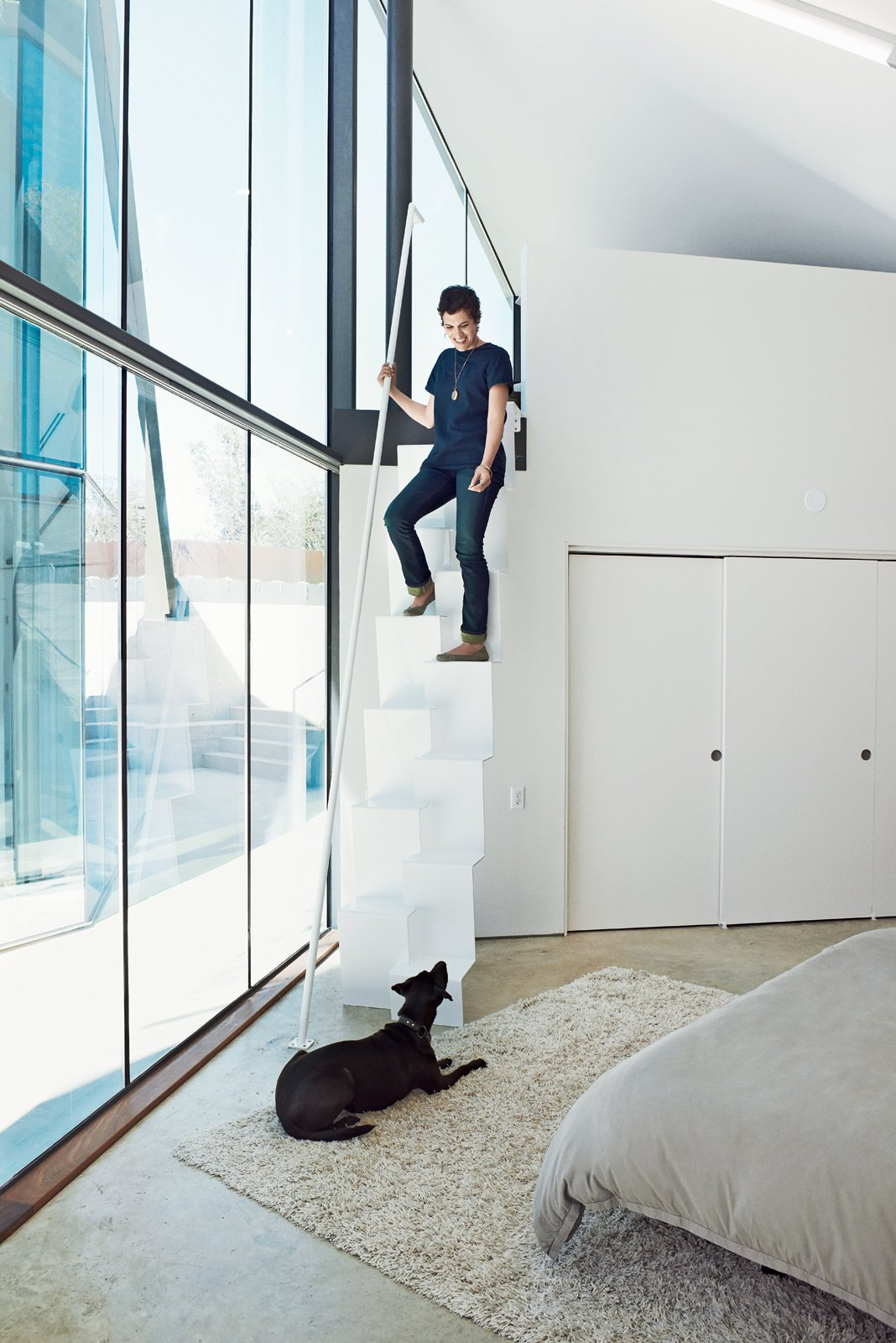 Like the pavilion holding the public spaces, the structure containing the bedrooms is clad in glass on the interior sides facing the courtyard, allowing a constant connection to the outside. Rodriguez (with dog Lupe) designed the steel stairs leading from the mezzanine-level home office to the master bedroom below. The stairs were fabricated by Austin-based Steel House MFG.  Bedrooms by Dwell from A Home Fit for a Science Fiction Writer