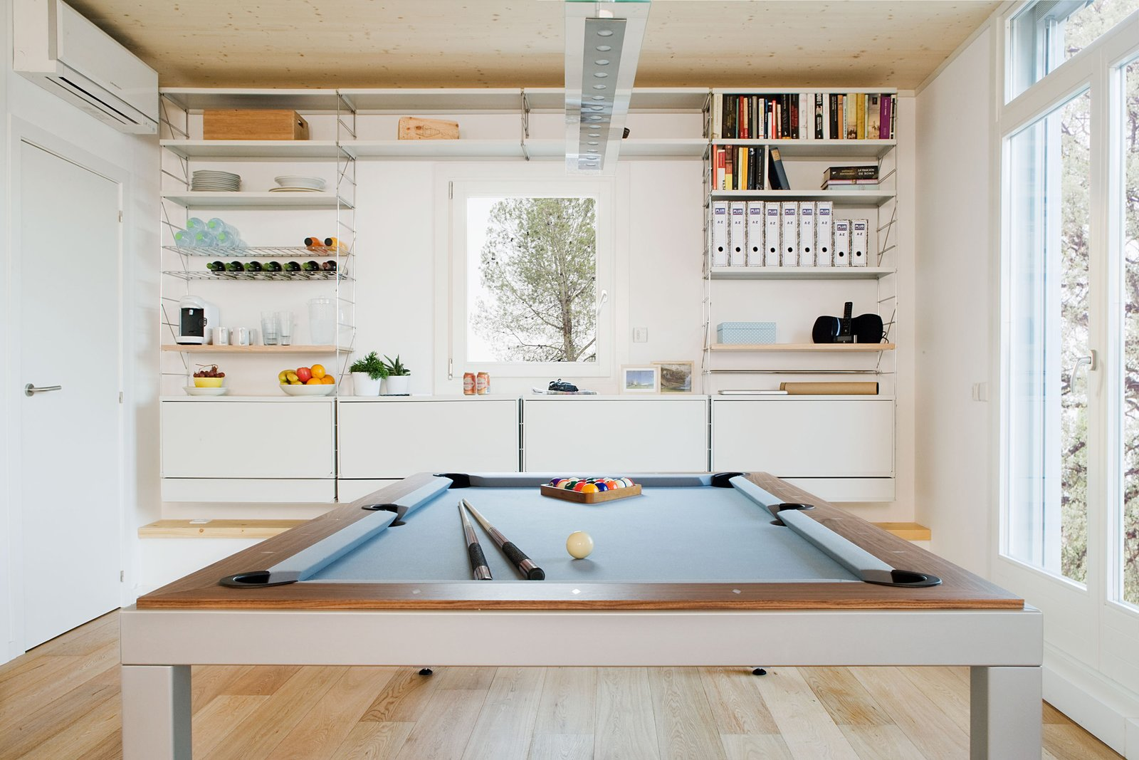 The dining room table transforms into a pool table for recreation.  Photo 5 of 7 in Plugged-In Prefab Collects Weather Data to Conserve Energy