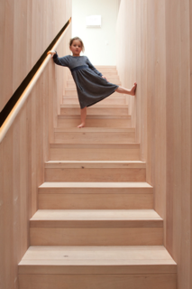 This Kid-Friendly Home is Full of Surprises - Photo 4 of 9 - Cooke treated the southern beech in the stairwell with natural oils, rather than polyurethane, to bring out the grain and warmth of the natural materials. To keep the surface visually clean and minimal, the balustrade is set into the wall, so wood wraps the stairwell from ground floor to skylight.