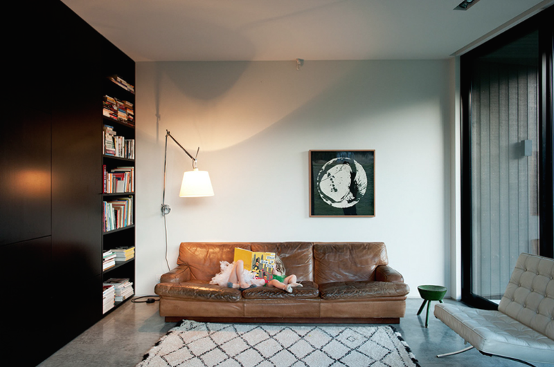 "The architect specifically chose a palette of natural finishes, including the polished concrete floor that flows the length and breadth of the ground level.  By way of contrast, the couple's eclectic collection of much-loved vintage furniture, including Mies van der Rohe Barcelona chairs, an Artemide lamp, and this 50-year-old sofa by mid-century Swedish designer Arne Norell, provide color and warmth. ""The bookcase also makes use of space to add layers of texture. Books are always a great addition to any interior,"" says Cooke.  The Beni Ouarain rug was purchased on a trip to Morocco."