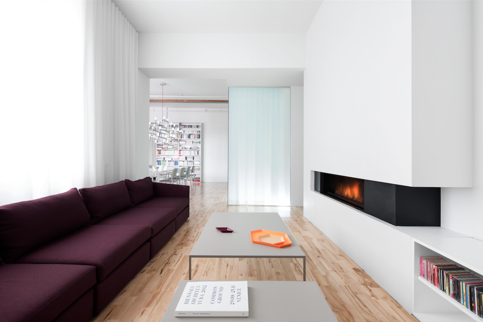 The minimal gas fireplace is from Ortal. Glass panels divide the living spaces, allowing natural light to carry through the space.  Luminous Modern Apartment in an Industrial Montreal Building by Allie Weiss