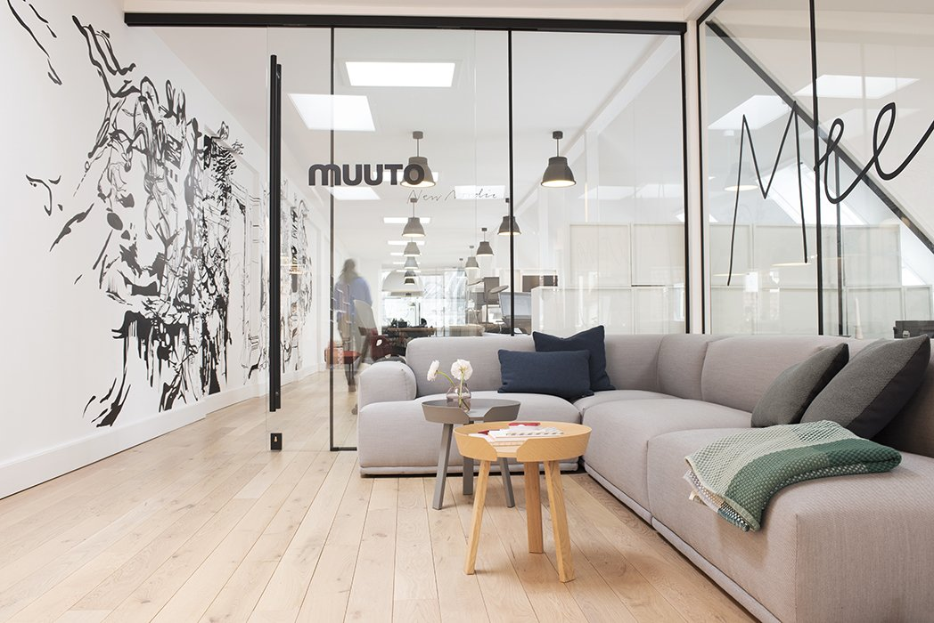 "Visitors to Muuto's headquarters are greeted by high-impact graphic wall art and wraparound glass walls. Brandt describes the look as ""Scandinavian with a New Yorker twist.""  Photo 1 of 7 in Muuto's Sophisticated Copenhagen Office is All About Transparency"