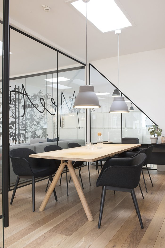 The subdued color scheme is also evident in the conference room. Floor-to-glass glass walls underscore the company's commitment to transparency, even in the most private spaces. The room is illuminated by grey Studio pendant lamps by Thomas Bernstrand.