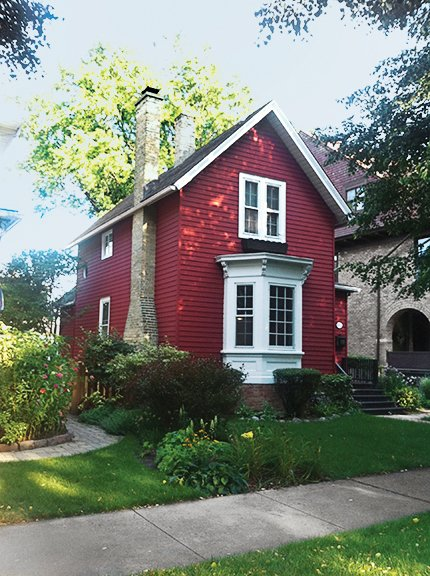 The existing house is a turn-of-the-century structure with a front bay window.