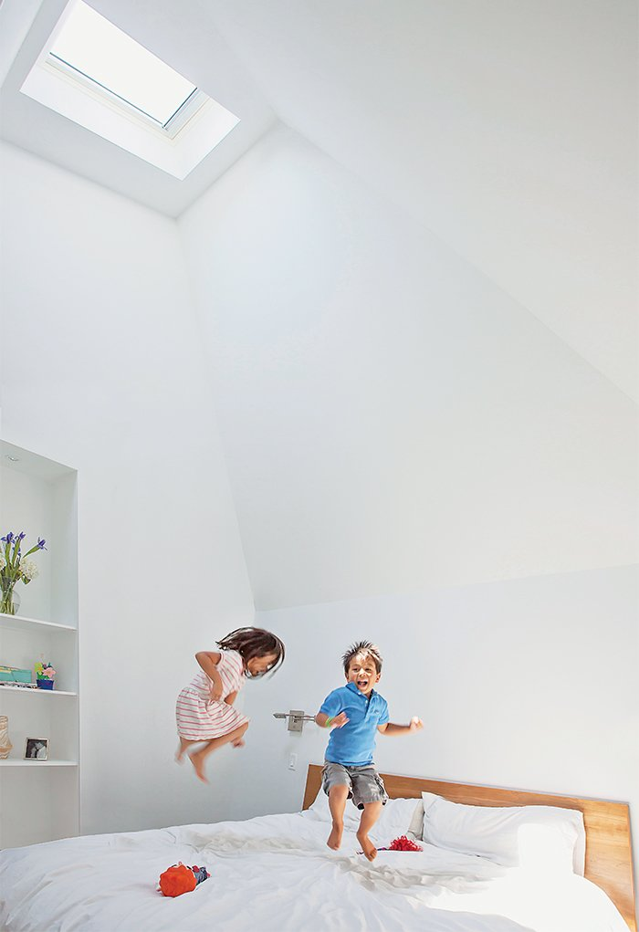 "Zoe and Jake horse around in their parents' new master bedroom. Issa says he vaulted the ceiling to fit under the addition's angular roofline for ""spatial impact."" Paint is Extra White by Sherwin-Williams.  Bedrooms by Dwell from This Farmhouse-Style Home Gets a Clever and Geometric Update"