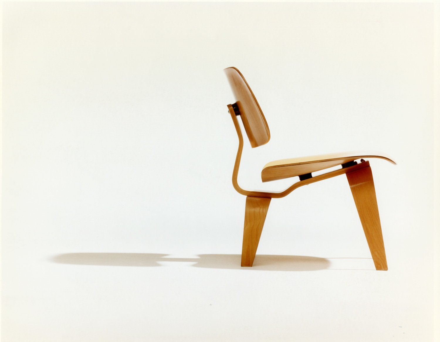 A photograph by Phil Schaafsma highlights the ergonomic design of the chair.  Photo 1 of 1 in Poll: Why Buy Real vs. Fake Furniture? from A Leg Splint Inspired Charles and Ray Eames' Famous Molded Plywood Lounge Chair