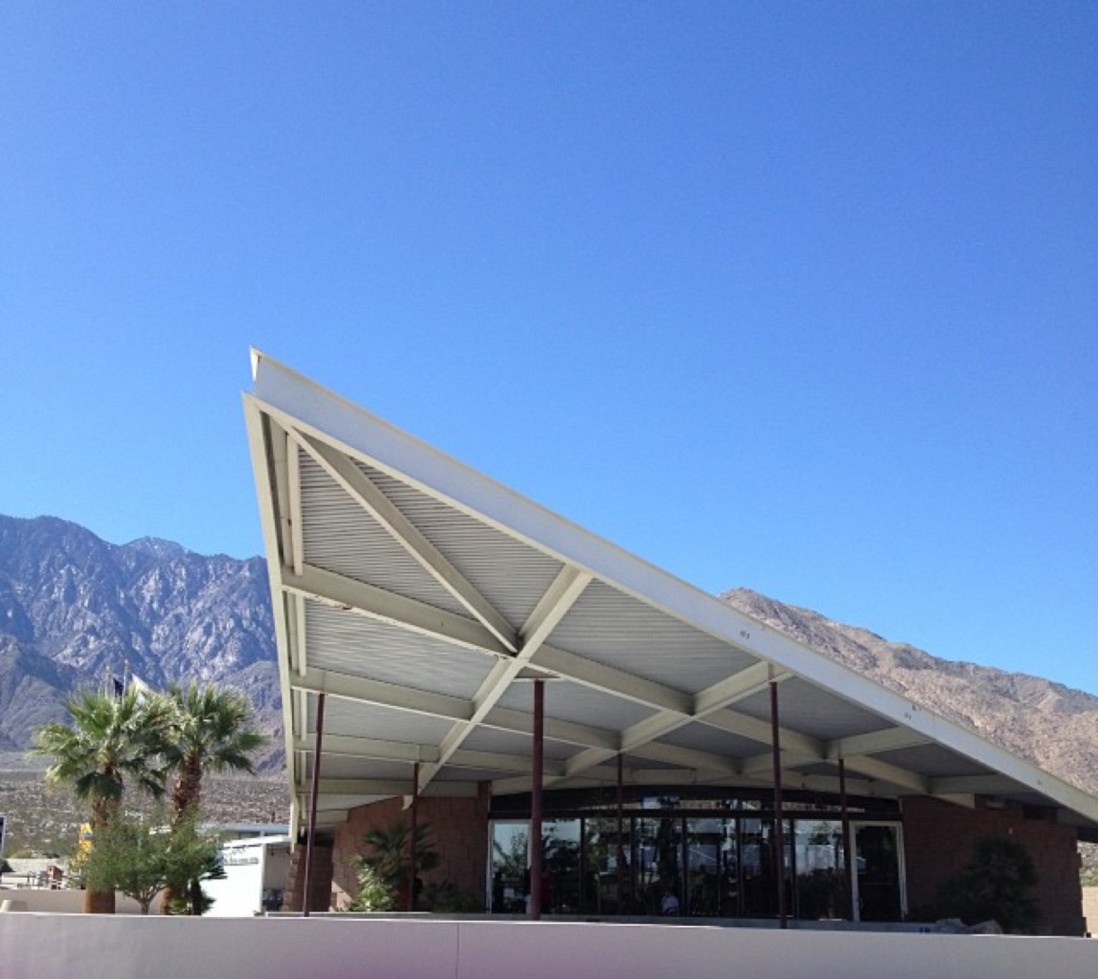 Visitors entering Palm Springs from other desert cities will first come upon the Palm Springs Tramway gas station, designed in 1965 by Albert Frey and Robson Chambers, topped by a hyperbolic paraboloid roof.