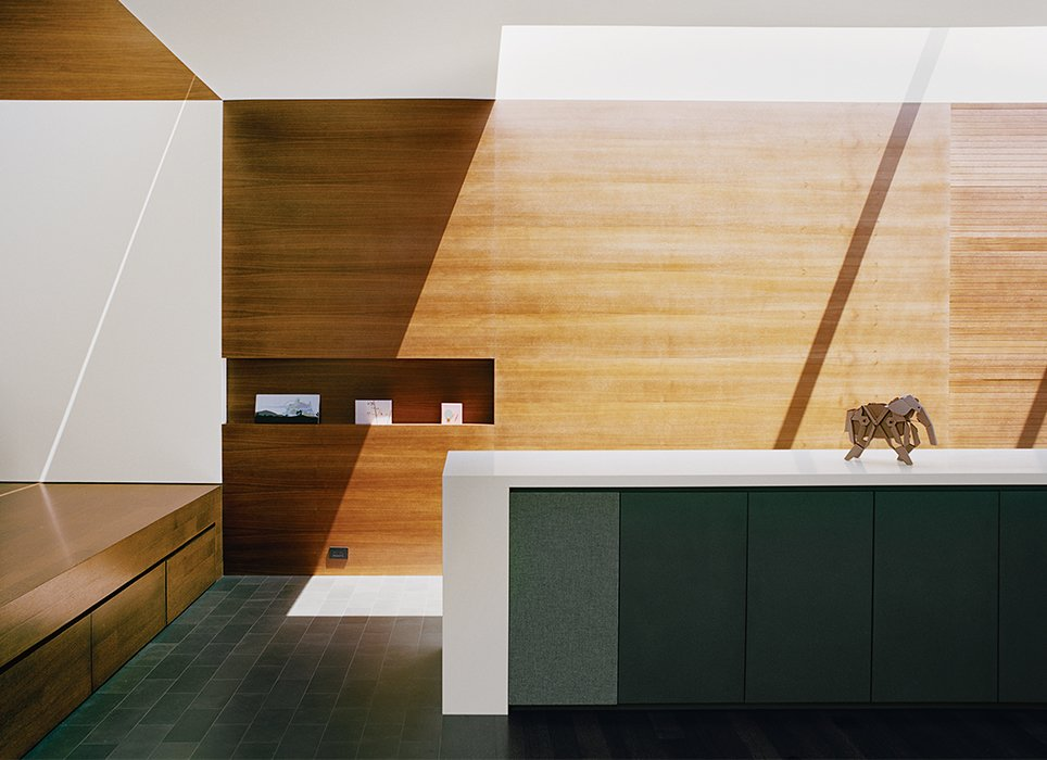 The residence architect Cary Bernstein designed for Scott Croyle and his family is an exercise in hide-and-seek. Clever storage keeps the space clutter-free and lets the structure shine. In the entryway, drawers tuck under the mezzanine, niches hold artwork, and speakers are built in line with the cabinets. Tagged: Storage Room and Cabinet Storage Type.  Photo 3 of 13 in A Meticulous Renovation Turns a Run-Down House Into a Storage-Smart Gem