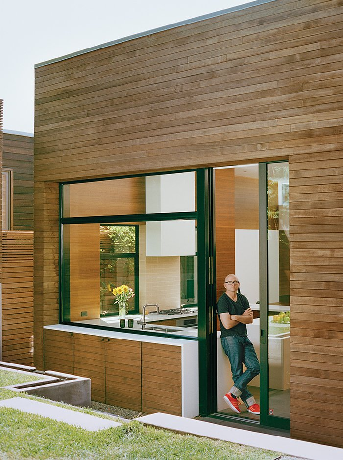 To reinforce a streamlined aesthetic, materials move from the inside out and from room to room. A Caesarstone countertop in the kitchen extends through a window to the backyard. The basalt path in the house continues outside and up the outdoor stairs. Tagged: Exterior, House, and Wood Siding Material.  Photo 8 of 13 in A Meticulous Renovation Turns a Run-Down House Into a Storage-Smart Gem