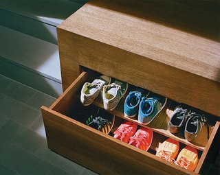 Generous storage is key to an uncluttered look. Drawers for shoes tuck away under the raised mezzanine floor.