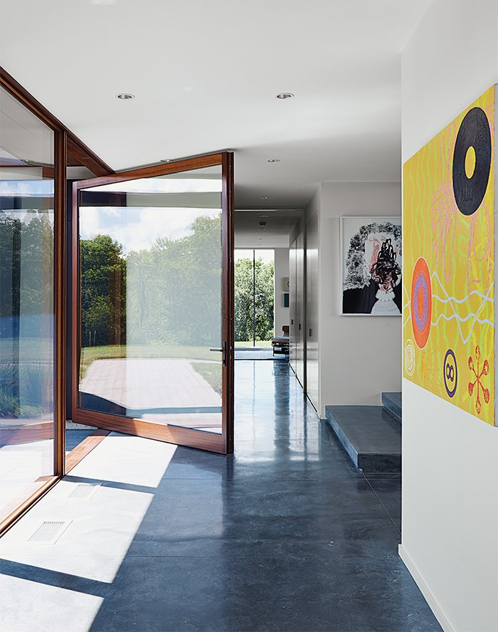 A custom pivot door by Archispec opens onto a foyer with a poured-concrete floor. The oil painting at right is by Derrick Buisch. Tagged: Doors, Exterior, Wood, and Swing Door Type.  Photo 2 of 10 in A Prairie Escape Embraces the Landscape with a Green Roof