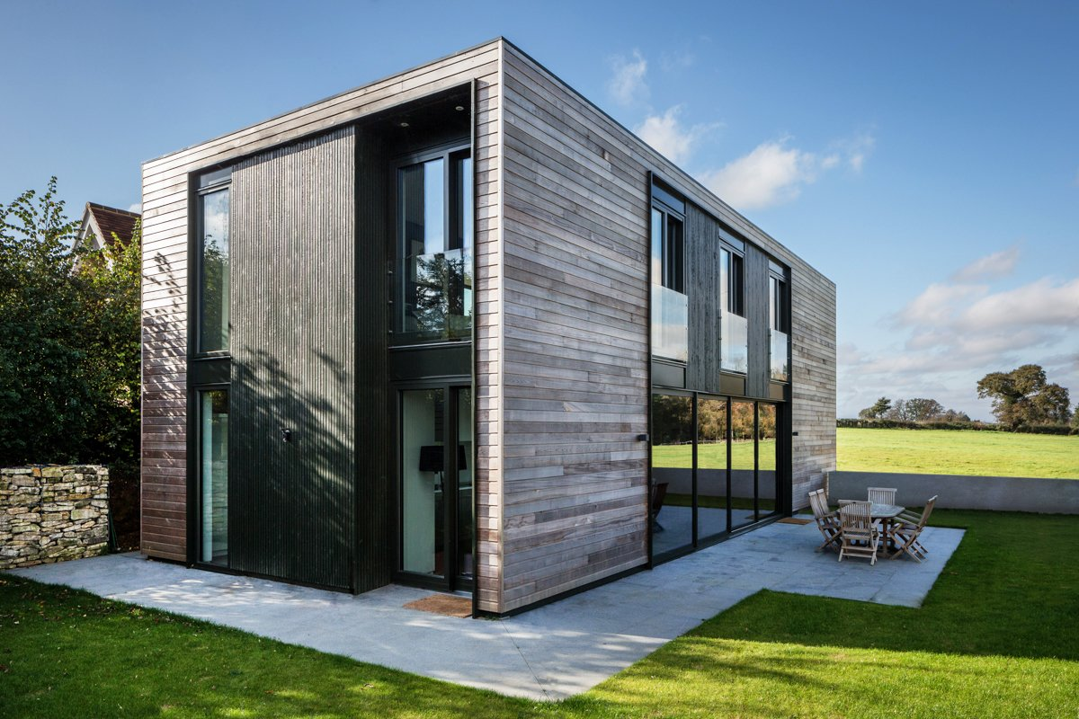 The house, which is located near Oxford, is clad in cedar. Composite timber and aluminum windows maintain the house's connection with the countryside, as does the generous patio that wraps around two of its sides.  Sandpath by David Rudin