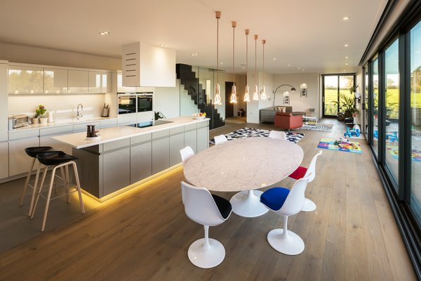 A white marble dining table and matching plastic chairs sit beneath copper pendants with Plumen light bulbs. On the other side of the open-plan living area, the sofa, table, and chairs, which predate the house, are perfectly integrated with their new surroundings. Photo 4 of Sandpath modern home