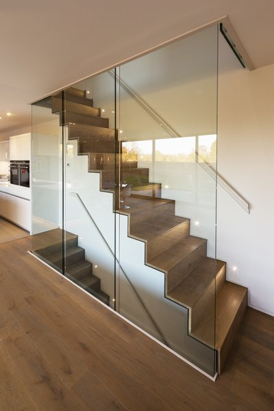 The home's ground level features engineered oak flooring. The staircase, which leads to the house's upper and lower levels, was constructed out of steel folded plate and subsequently clad in timber. Photo 6 of Sandpath modern home