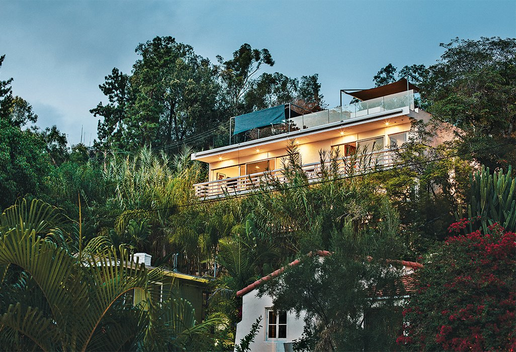 The house opens to the rear deck, which the original architects projected into the setback to maximize the outdoor space. All the doors are from Western Window Systems. As in his own home in Venice, Dimster added a clear railingto the roof deck, so nothing would obstruct the view. He also designed the sun shades.  Photo 4 of 15 in A Midcentury Home Enjoys Views from Every Angle