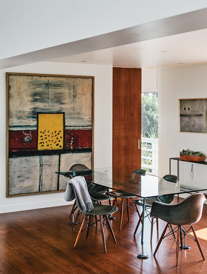 In the dining room, artworks by Alan Davie (at left) and Martin Bradley join a Norman Foster dining table.  Photo 14 of 15 in A Midcentury Home Enjoys Views from Every Angle
