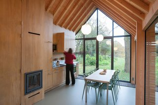 This Light-Filled Cabin in the Netherlands Is Completely Made by Hand - Photo 7 of 9 - Fine wood craftsmanship defines the dwelling's interior, where all the facilities—from the kitchen cabinets to the fireplace to the bathroom—are integrated into a single oak wall, handmade by van Norel. He also made the dining table, which is paired with Philippe Starck master chairs—the only ready-made items in the space other than fixtures and appliances.