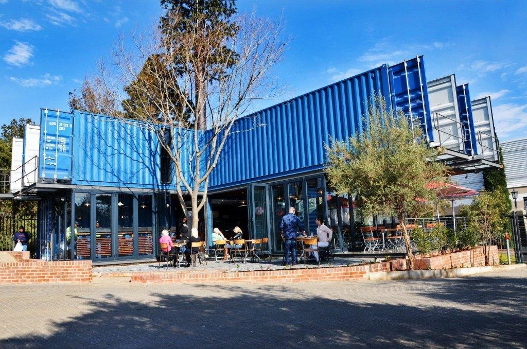 The alignment of the shipping containers creates a courtyard for outdoor seating away from the street.  Amazing Examples of Shipping Container Architecture by Diana Budds from A Coffee Shop Made With Shipping Containers in South Africa