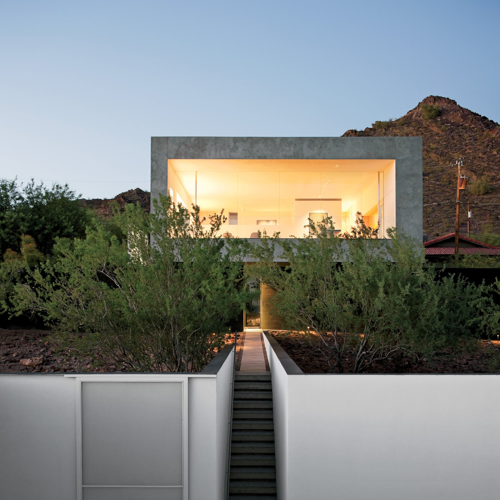 """The challenge was to render the site whole again after the original owner 'bladed' most of the creosote bush,"" explains Debra Burnette, who concieved the landscape design. Tagged: Exterior and Concrete Siding Material.  Photo 3 of 8 in This House Doesn't Hold Back and Embraces the Desert"