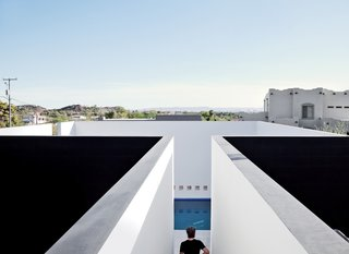 "This House Doesn't Hold Back and Embraces the Desert - Photo 5 of 8 - The pool is sheltered on all sides by white plaster walls, a space envisioned by the architect as a volume that's ""half terrace, half cool-water retreat...projected toward the canopy of the desert sky."""