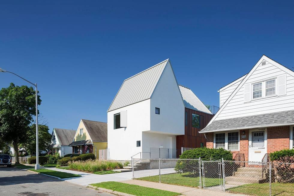 """With clean white stucco cladding and unusual angles, the three-module house stands out from the surrounding neighborhood, which features mostly post-war, one-and-a-half story homes.  All the """"Right"""" Angles by Matthew Keeshin from Three Unique Homes Fit Under One Roof for an Extended Family in Queens"""