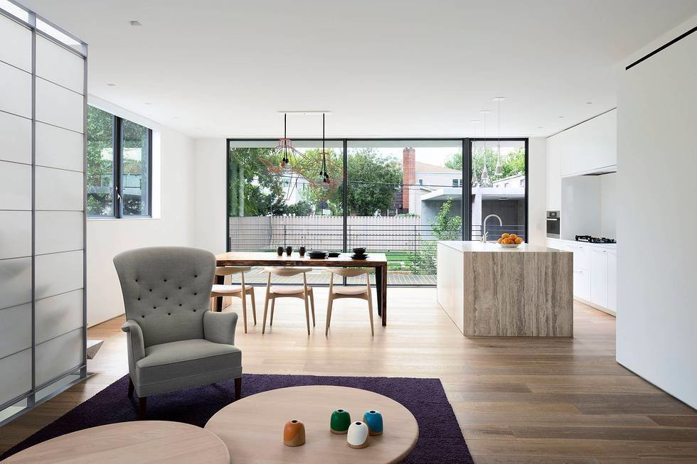 The client's house, located in the center of the building, caters to the couple and their two children. The clean, understated kitchen features a hulking travertine island and views of the garden below. Homes for the Whole Family  by Matthew Keeshin