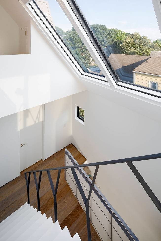 A thin Y-shaped metal banister guides movement up the stairs to the client's son's room. Below the Corian stairs, an office nook was carved out of the wall in the daughter's room.  190+ Best Modern Staircase Ideas by Dwell from Three Unique Homes Fit Under One Roof for an Extended Family in Queens