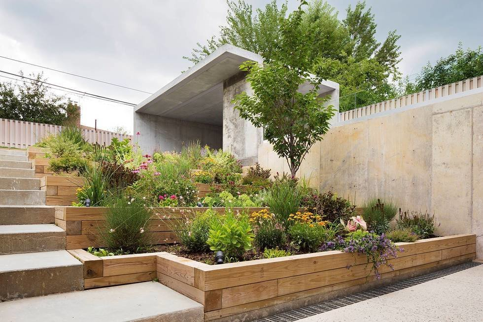 The backside of the lot was dug out to create a recessed garden for privacy. The mother is an active cook, so including planter boxes for herbs and hot peppers was a must.