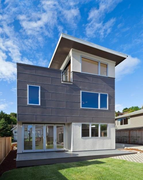 "The couple desired a new home that would suit their eco-conscious lifestyle. On their must-have list was a location close to Seattle's recreational-friendly Greenlake, a large roof deck, eco-friendly materials that reduced their carbon footprint, and surprisingly, no garage. ""It is a modular home, so basically you're saving a lot of money on the [construction] time,"" says the team behind Greenfab, which served as general contractor for the project. ""Your construction costs are also way lower."" Tagged: Exterior, Prefab Building Type, Metal Siding Material, and House.  Prefab Homes by Dwell from Energy-Efficient Prefab Responds to Seattle Climate"
