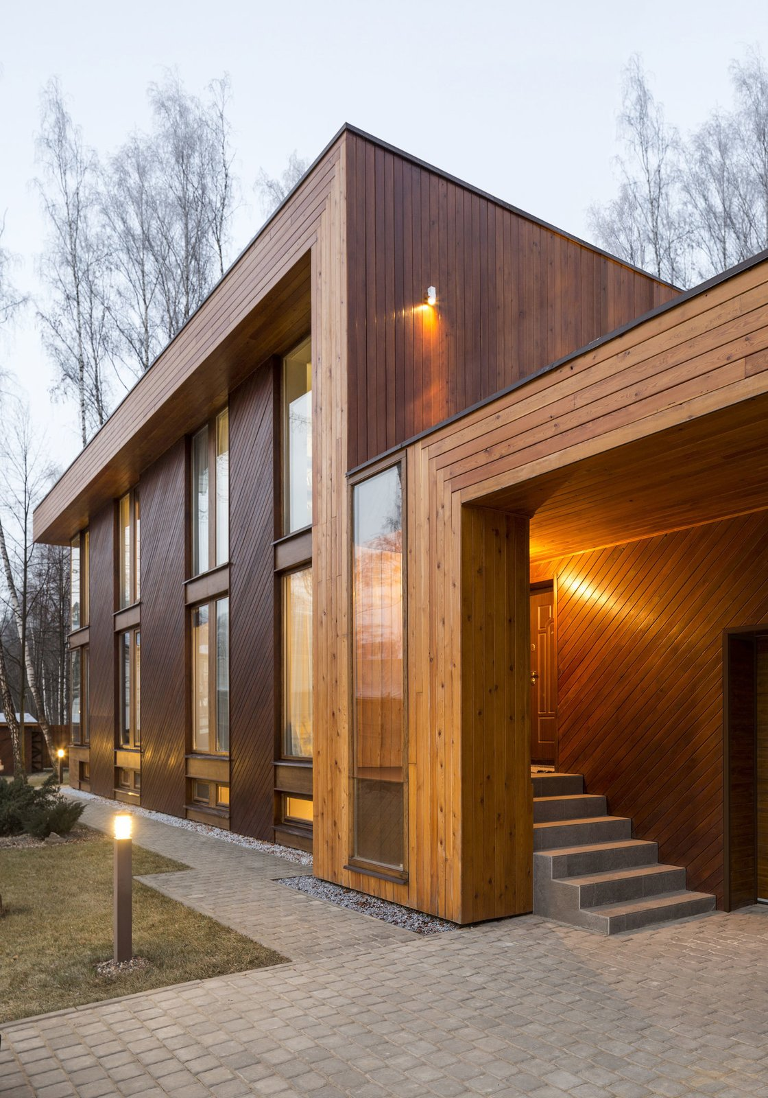 "Larch timber planks make up the reddish-gray facade and also adorn the interior walls and floor. Zhidkov says the wood ""allowed the house to be an organic insertion into the landscape.""  House in Moscow by Laura C. Mallonee"