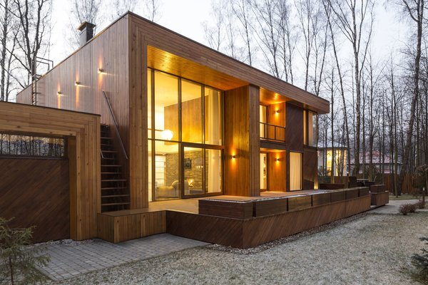 The house has two distinct volumes. The smaller one contains the garage, as well as the heating and air conditioning units, and is topped by a green roof garden accessible by an outdoor staircase. The larger, two-level volume sits slightly above ground and contains the living, dining, and sleeping spaces—all with windows facing east into the forest. Photo 3 of House in Moscow modern home