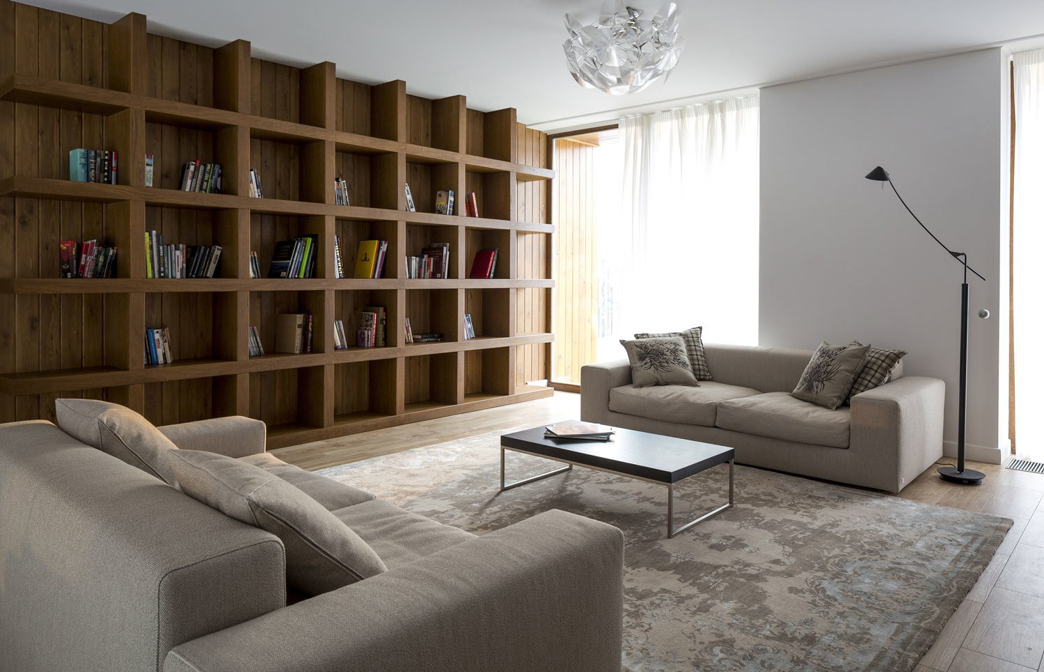A built-in larch bookshelf occupies an entire wall on the second floor den.