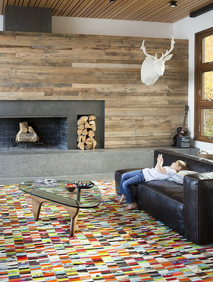 When building their dream retreat in Jackson Hole, Wyoming, Steve and Alexi Conine worked with architect Brad Hoyt to create a smart house that fused technology and design. Like the rest of the home, the living-room furnishings blend high design, comfort, and kid-friendliness, including a table by Isamu Noguchi for Herman Miller, a leather sectional sofa from Four Hands, a cashmere cableknit-covered elk mount by Rachel Denny, and a custom, multicolored cowhide patchwork rug by Linie Design. Tagged: Living Room, Sofa, Coffee Tables, Wood Burning Fireplace, and Standard Layout Fireplace.  Photo 3 of 11 in A Custom, LED-Lit Slide Twists Through This Family-Friendly Vacation Home