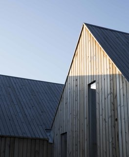 With their matching peaked roofs, every cabin nods to the traditional form of countryside retreats. The cluster's pine cladding has been treated to speed up the aging process, giving it a warm patina.