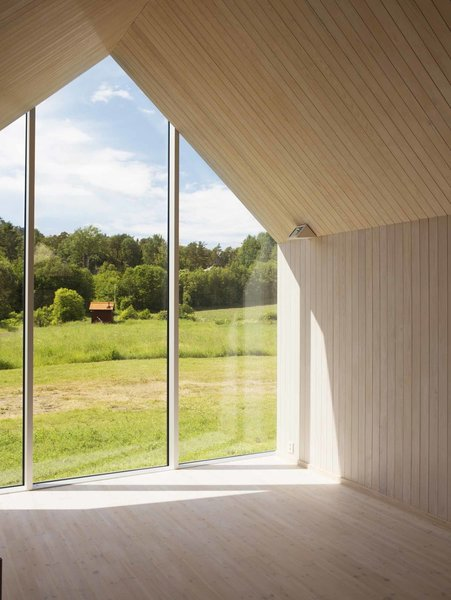 Full-height glazing caps the central living area. A rigid steel frame concealed within its wood envelope allows for uninterrupted sight lines and creates a single, open-plan living space.