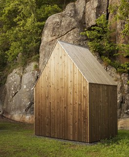 101 Best Modern Cabins - Photo 23 of 101 - A shed provides storage for the owners' tools as well as wood for the fireplace. It features the same aged pine finish as the main home.