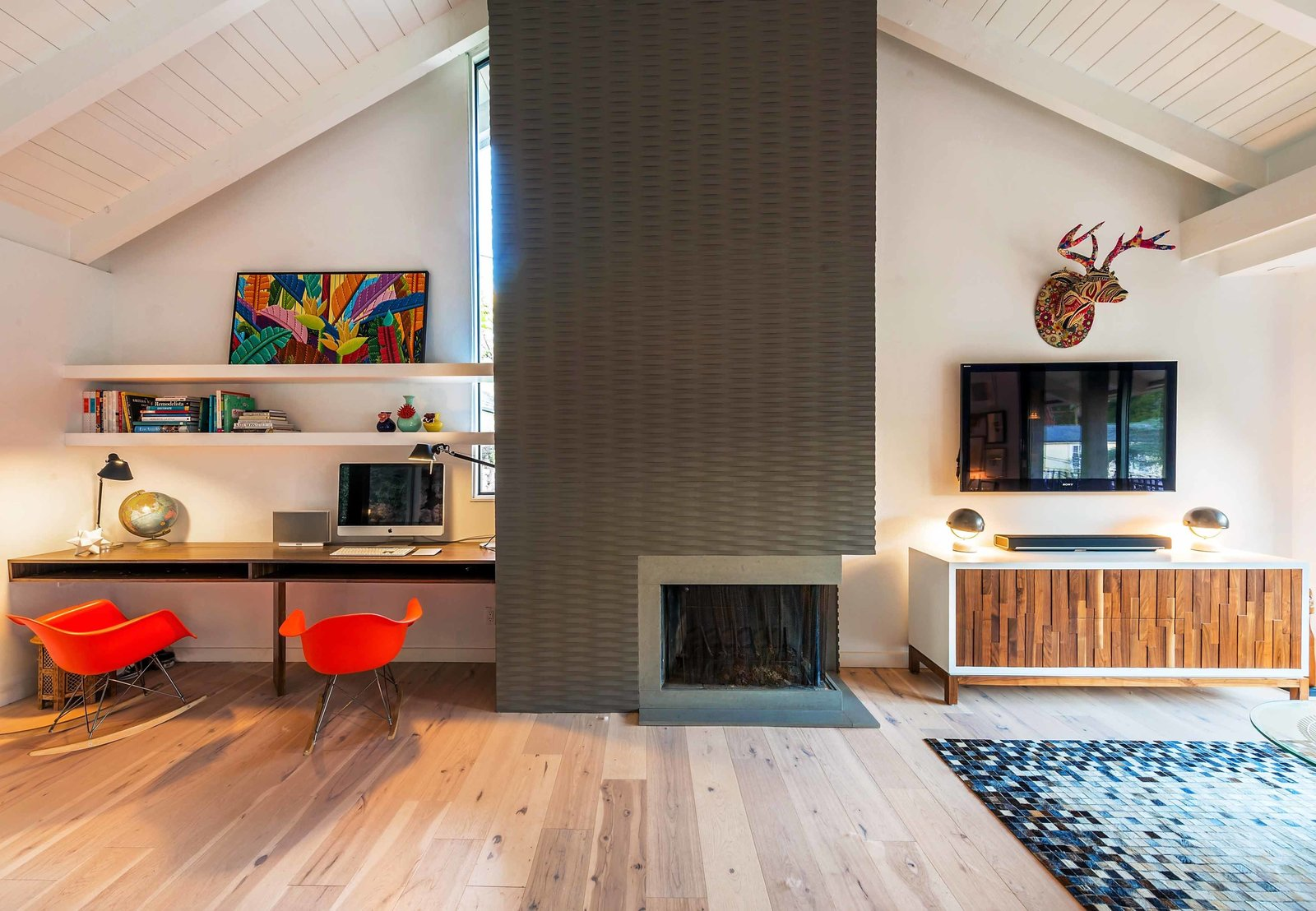 The fireplace is a custom-made, three-dimensional feature that stands in stark contrast to the soft woods and white walls that make up the rest of the room. The small office nook features a custom walnut built-in desk, painted white.  97+ Modern Fireplace Ideas by Dwell from Playful Materials Refresh a Dated Hollywood Home