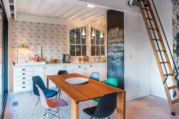 The kitchen is just as detailed and eclectic as the rest of the main floor, with a wall-sized chalkboard and retro wallpaper accenting the streamlined white cabinetry. Bright, colorful dining room chairs add whimsy.
