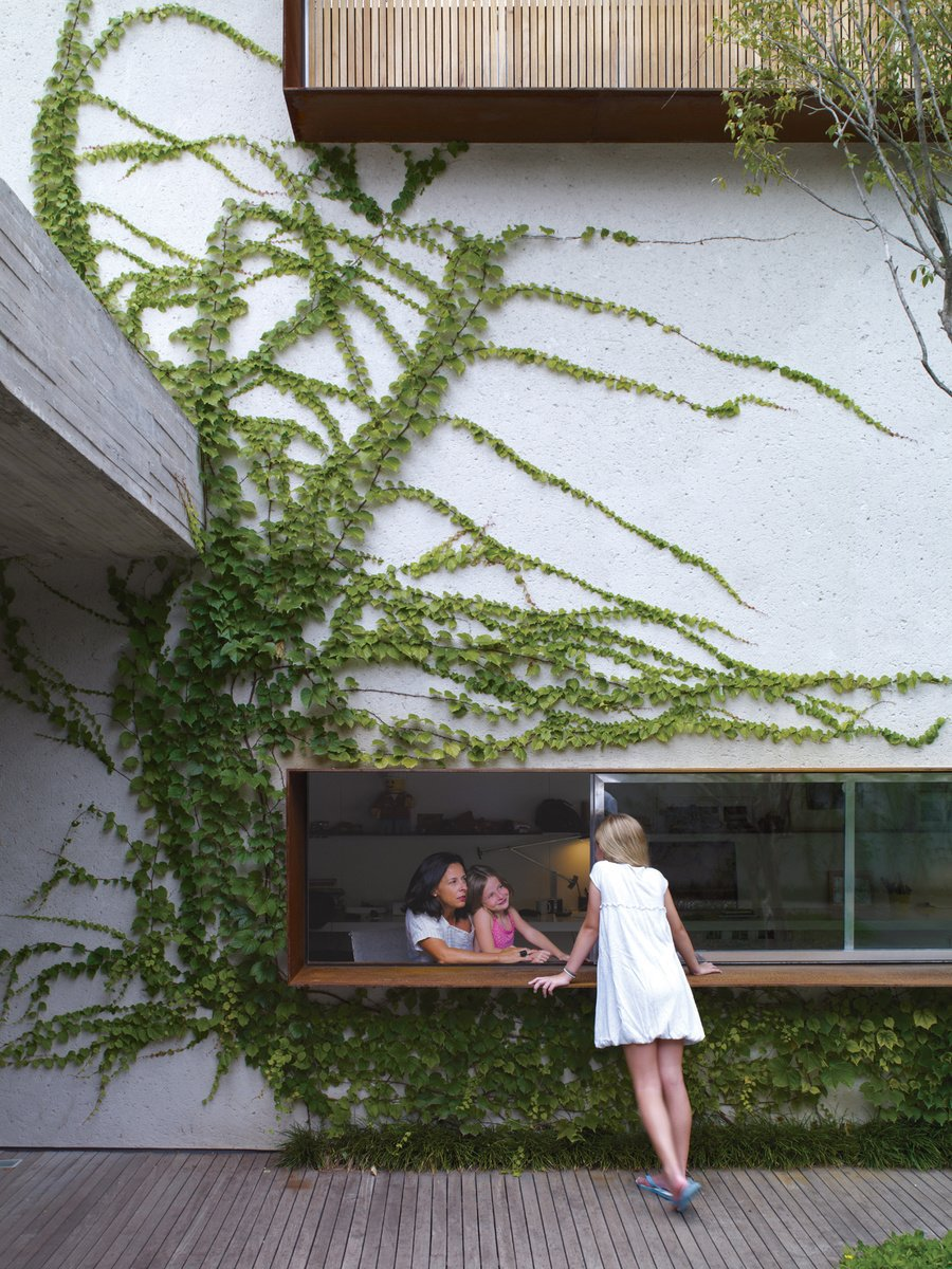 From the garden deck, Sophia Cóser talks to sister Helena and mother Piti through a wide, low-slung window typical of architect Marcio Kogan. Photo by Cristobal Palma.
