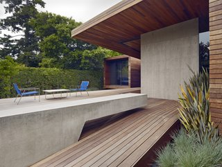 An Indoor-Outdoor Renovation for a 1950s Ranch House in the Bay Area - Photo 3 of 8 - A spacious deck was created as part of the addition. A cantilevered concrete bench stretches out to the rear garden and complements the adjacent concrete wall.
