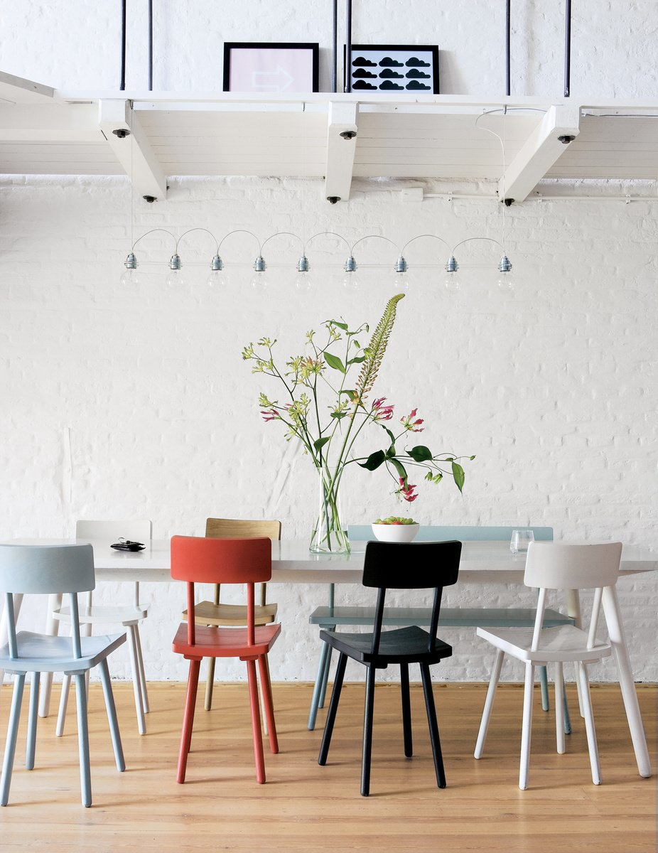 Piet Hein Eek's wooden chairs add a touch of color to the monochromatic Amsterdram apartment of Hunter Hindman and Shelby Carr. Tagged: Dining Room, Chair, Table, and Medium Hardwood Floor.  Photo 8 of 41 in 50 Dashing Dining Rooms from Musical Chairs
