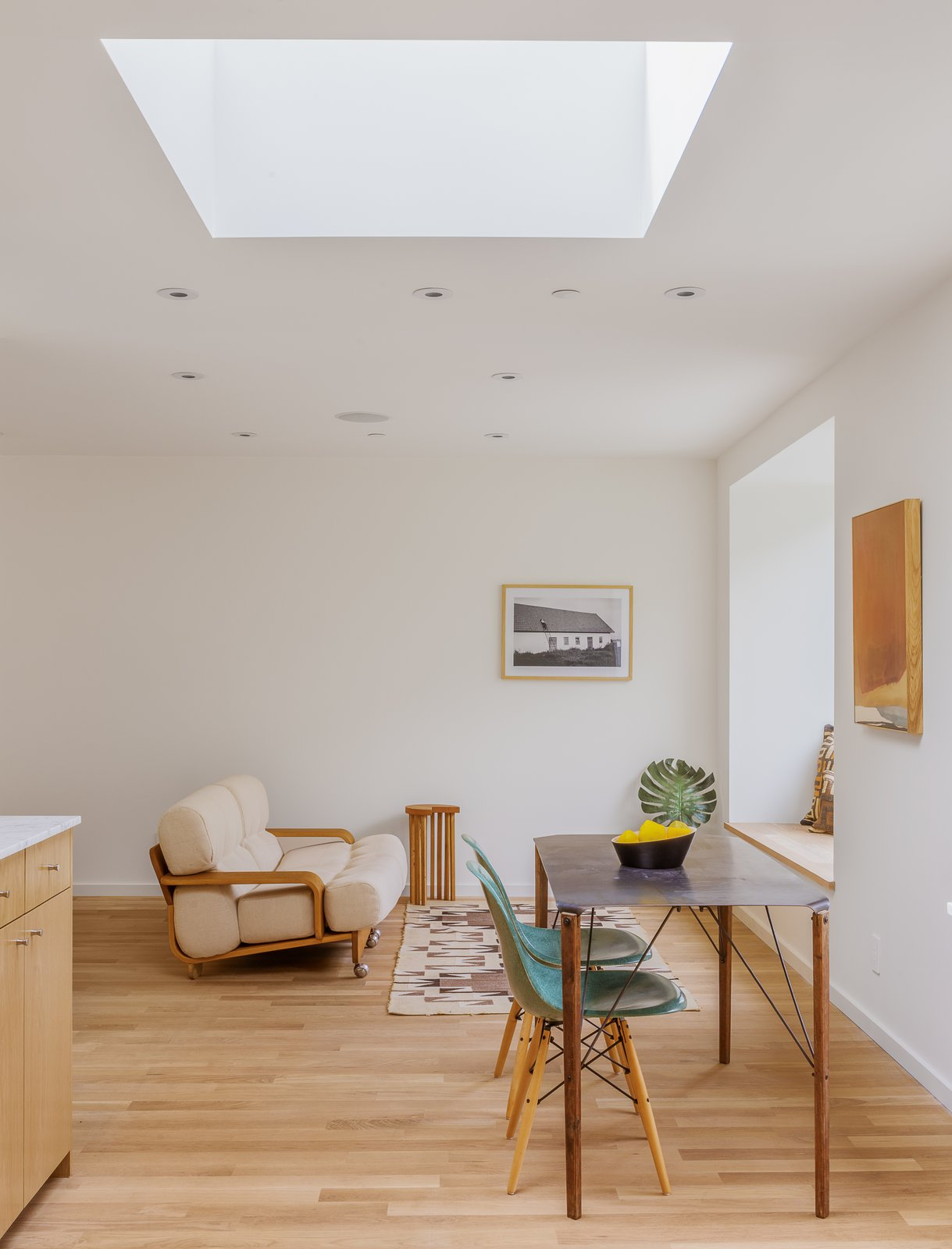 Skylights add to the apparent volume of the space, as well as performing the practical duty of providing light.  Photo 5 of 9 in Twin Houses on Tiny Lots Stretch Outward for Space