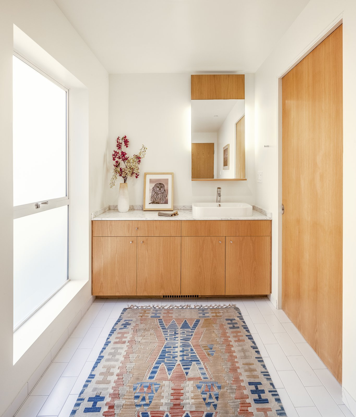 The architect has a track record of stripping away elements of excess to create simple, livable, and well-lit spaces that feel larger than they are. This downstairs bathroom features a simple white ceramic tiles and a sliding white oak door.